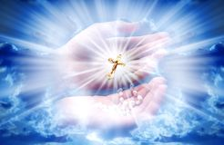 Christian cross with light. Composite of hands holding a cross against a sky with divine light stock illustration