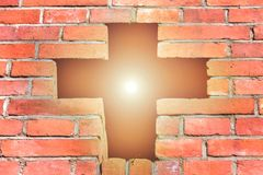 Christian cross made of bricks, a bright cross is shining through the bright sun, faith in God. Christian cross made of bricks, a bright cross is shining through stock photo