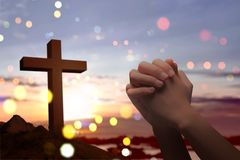 Christian cross and male hands with praying position. Over sunset background stock photo