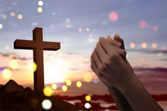 Christian cross and male hands with praying position. Over sunset background royalty free stock photo