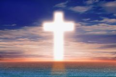 Christian Cross in the middle of the sea. With a backdrop of sunset royalty free stock photos