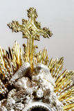 Christian Cross in monstrance. Vertical photo in color about a close up of a mostrance made of metal, focused in the cross with shallow Depth Of field Royalty Free Stock Photos