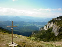Christian cross on mountain. Cross on the top of a mountain with cloudy blue sky Romania royalty free stock image