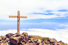 Christian cross on mountain top. Christian wooden cross on mountain top, rocky summit, beautiful inspirational landscape with ocean, island, clouds and blue sky Stock Photos