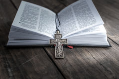Christian cross necklace  lying on an open page of the bible. Stock Photography