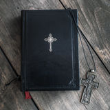 Christian cross necklace next to holy Bible Stock Images