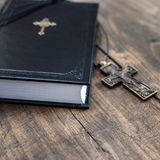 Christian cross necklace next to holy Bible Royalty Free Stock Photography