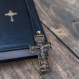Christian cross necklace next to holy Bible Stock Photos