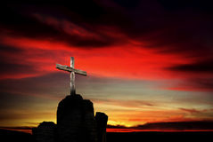 Christian cross over dark red sunset background Stock Photos