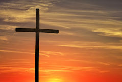Christian cross over dark red sunset background Stock Images