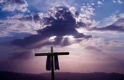 Christian cross over dark sunset background Royalty Free Stock Image