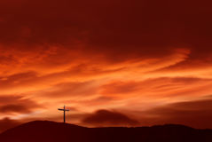 Christian cross over red sunset background landscape Stock Image