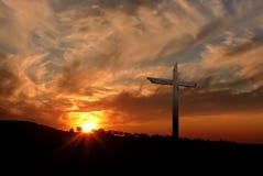 Christian cross over sunset background. Silhouette of Christian cross at sunrise or sunset with light rays Stock Photos
