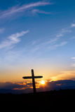 Christian cross over sunset background vertical image Royalty Free Stock Image