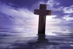 Christian cross with reflected on the water. Over dramatic sky background Royalty Free Stock Images