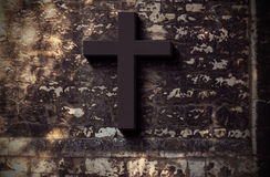 Christian Cross - religion concept. Black Christian cross on dark grunge wall - religion and belief concept Stock Photos