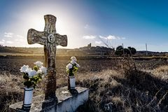 Christian cross in a roadside ditch. With flowers. Monument, symbol.Entrance symbol to a small population of Spain.n Stock Image
