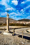 Christian cross in a roadside ditch. With flowers. Monument, symbol.Entrance symbol to a small population of Spain.n Stock Photos