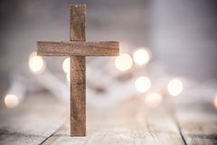 Christian Cross on a Soft Bokeh Background. A wooden Christian cross on a soft bokeh light and wood background stock images