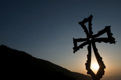 Christian cross at sunset with mountain backdrop. Metal Christian cross glowing at sunset, with fading sun shining through it and mountain backdrop, Montseny Stock Photos