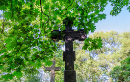 The Christian cross. The cross is the symbol of the Christian faith. High cross on a background of green foliage and blue sky. Crosses on the background of Royalty Free Stock Photography