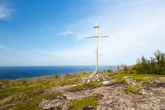 Christian cross on top of the mountain. Christian wooden cross on top of the mountain, island in the white sea stock image
