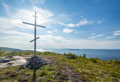 Christian cross on top of the mountain. Christian wooden cross on top of the mountain, island in the white sea royalty free stock photo
