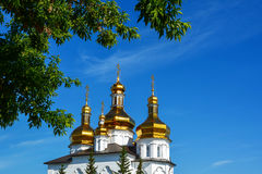 Christian Cross which is visible through the tree leaves. White church, orthodox, Russia, blue sky, view Stock Photo