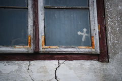Christian cross in the window. Of the old house Stock Photo