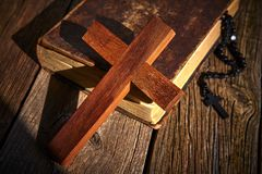 Christian cross on wood bible and rosary. Beads over wooden vintage background royalty free stock photography