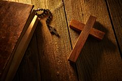Christian cross on wood bible and rosary. Beads over wooden vintage background royalty free stock images