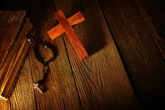 Christian cross on wood bible and rosary. Beads over wooden vintage background stock images