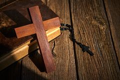Christian cross on wood bible and rosary. Beads over wooden vintage background royalty free stock image
