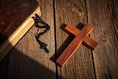 Christian cross on wood bible and rosary. Beads over wooden vintage background stock photos