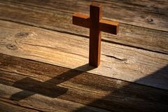 Christian cross on wood over wooden. Background vintage with shadows royalty free stock photo
