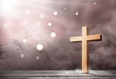 Christian cross on the wooden table with light. Over bright background stock image