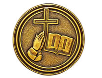 Christian Education. Bronze medallion with a cross, praying hands and a book or the Holy Bible embossed.  May be used as a symbol of education or religion Royalty Free Stock Photos