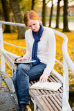 Christian Faith - Reading the Bible. Woman studies the Bible online with a tablet from a city park in the autumn Royalty Free Stock Photos