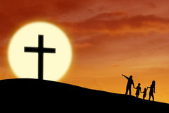 Christian family at the Cross. Silhouette of a Christian family walking toward Cross sign during sunset stock photography