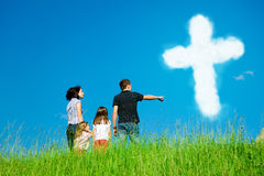 Christian Family Looking At Clouds Forming The Holy Cross. A family with 2 daughters are standing at the top of a grassy hill, pointing at clouds forming the Stock Photography