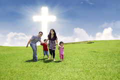 Christian family running in park. Christian family is running over the green field under bright Cross sky Stock Photos