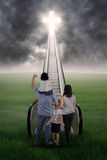 Christian family on the stairs. Christian family are standing on the stairs and looking at the bright Cross royalty free stock photo