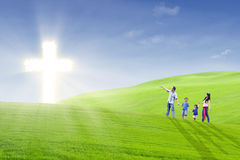Christian family walk toward the light. Family members are walking happily towards bright cross in the park Royalty Free Stock Image