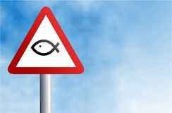 Christian fish sign. A traffic warning sign featuring a Christian fish icon against a sky background Royalty Free Stock Image