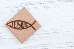 Christian fish symbol carved in wood on white vintage wooden background Stock Photos
