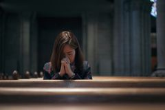 A Christian girl is sitting and praying with broken heart in the. A Christian girl is sitting and praying with humble heart in the church stock images