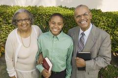 Christian Grandparents y nieto en el jardín que sostiene el retrato de las biblias Foto de archivo libre de regalías