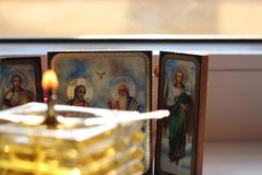 Christian icons and blurred oil candle. Christian orthodox icons in the back of a blurred homemade glass oil candle Stock Image