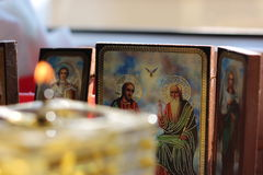 Christian icons and blurred oil candle. Christian orthodox icons in the back of a blurred homemade glass oil candle Royalty Free Stock Images