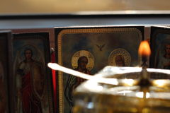 Christian icons and blurred oil candle. Christian orthodox icons in the back of a blurred homemade glass oil candle Stock Images
